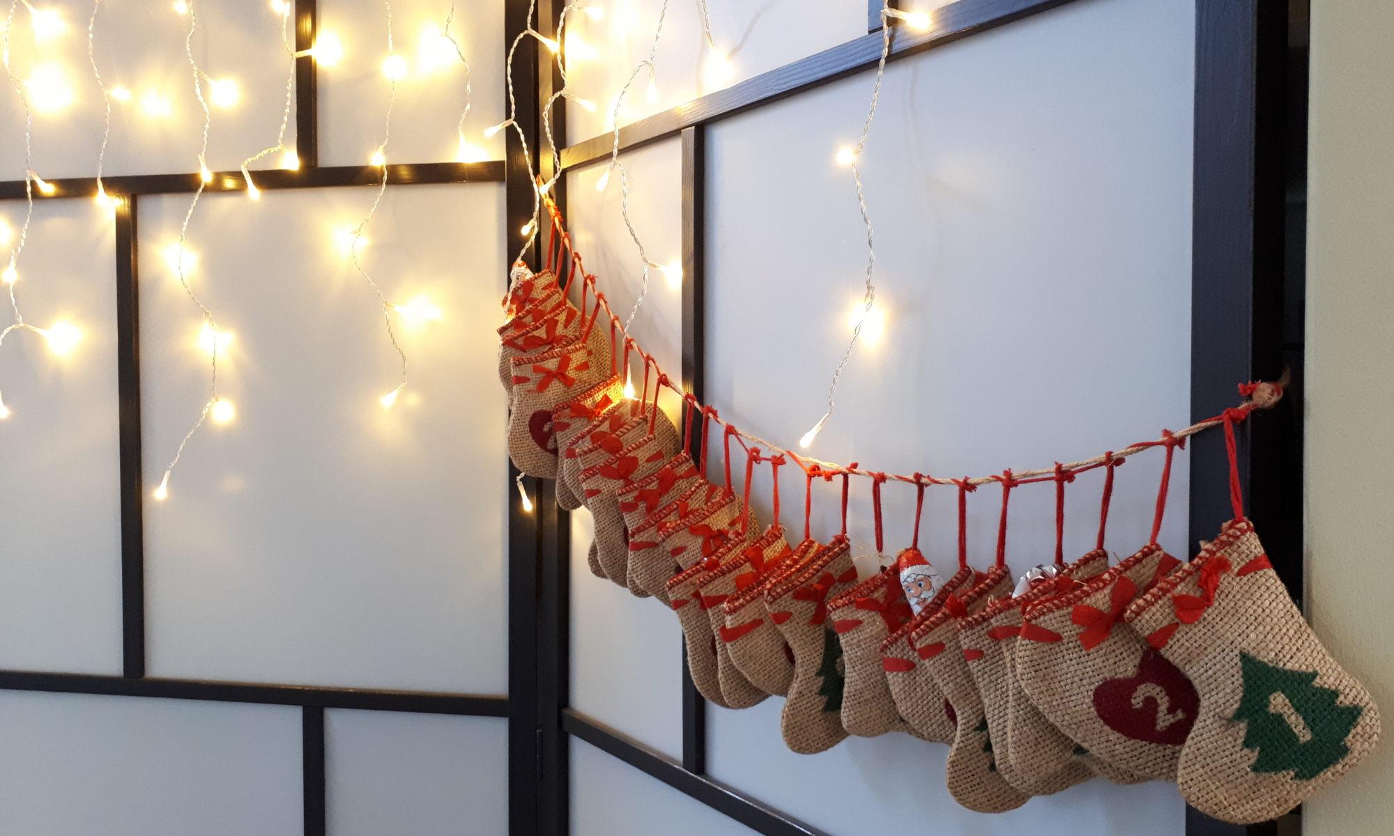 Adventskalender in Jurtesäckchen vor einer Spanischen Wand mit Lichterkette