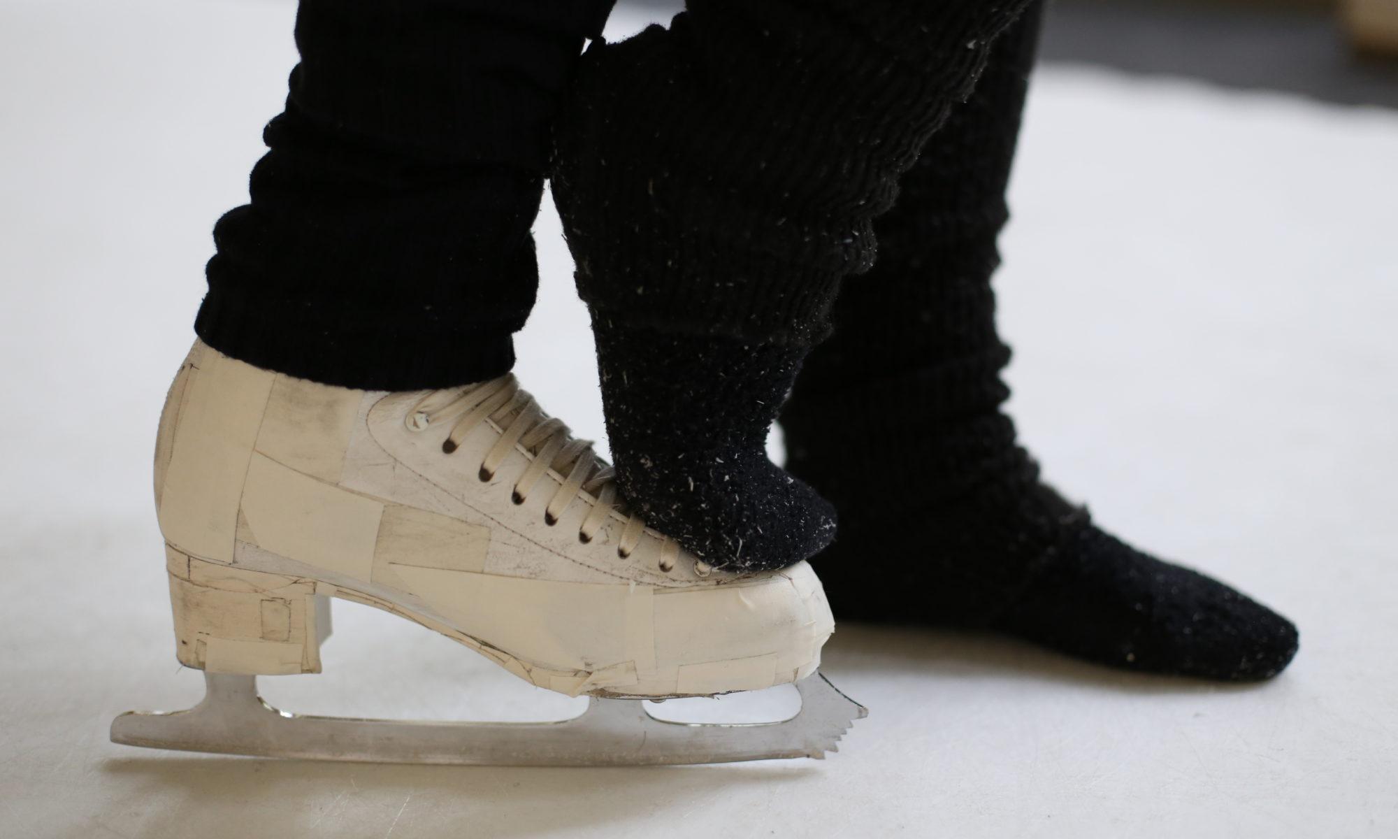 ein Schlittschuh auf Kunststoffeis auf dem ein Fuß steht